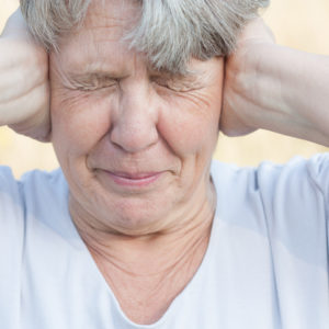 senior woman covering ears