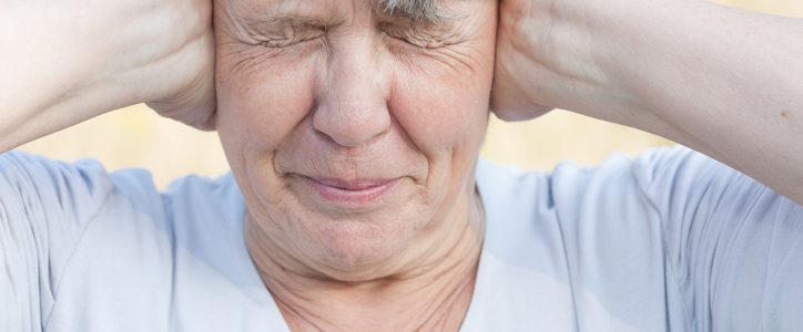 senior woman covering ears