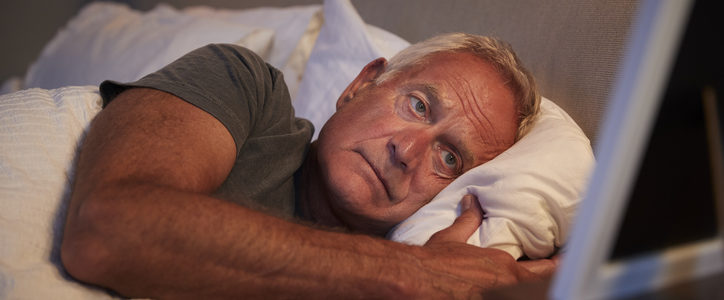senior man lying in bed